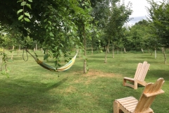 Hamac et chaises longues en bois dans le jardin arboré de la Tiny House